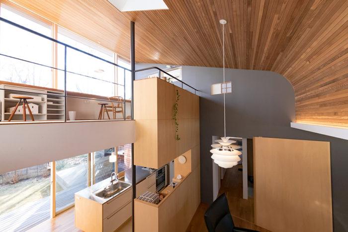 グレーの壁を境に、1階、2階ともに奥がプライベートスペース、手前がパブリックスペース。壁は南(左)に向かって開いている。