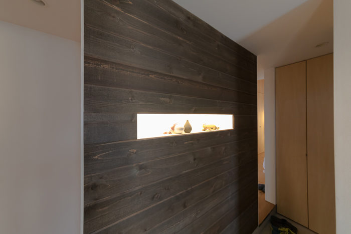 玄関を入って正面にはレッドシダーの壁が。奥がプライベートスペースでシューズクローゼットを設置。手前がリビングへと続く。