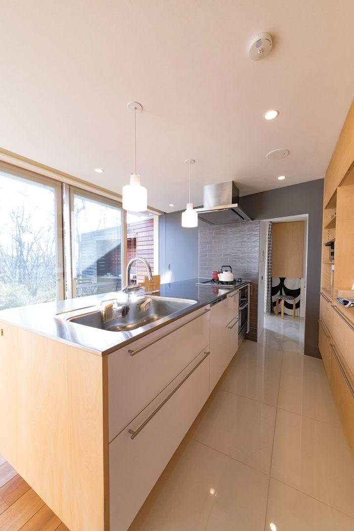 キッチンの奥が家事ゾーン。冷蔵庫や洗濯機が置かれ、バスルーム、寝室へと続く。