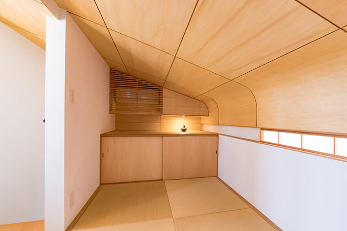 3畳ほどの和室。低めのR天井、細めの障子窓などこだわりがのぞく。奥(下)には布団を収納。天井のカーブに沿って上部にも収納を設けた。