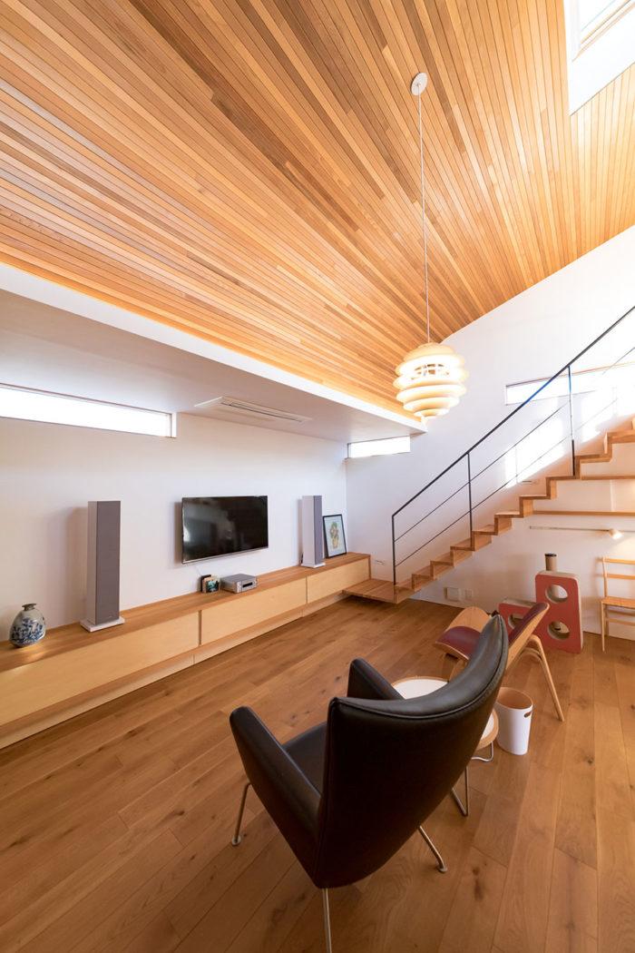 細めにカットしたレッドシダー材の天井が美しい。トップライトからも十分な光が注ぐ。宙に浮いた片持ち階段もスタイリッシュ。