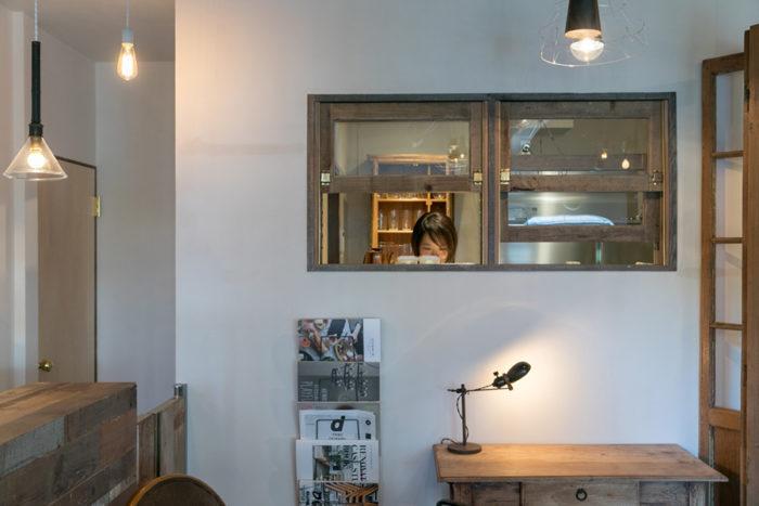カフェスペースと調理場は、古い電車の窓のような、持ち上げて開くスタイルに。金色の金物も美しい。