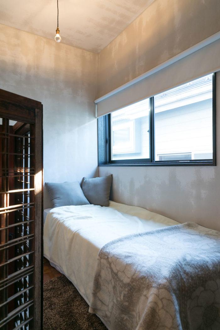 チェストの後ろをベッドスペースとしている。「光が天井に当たるハーフミラー電球は、明るすぎないのでベッドの上の照明としては最適でした」 窓には遮光のロールスクリーンを採用。