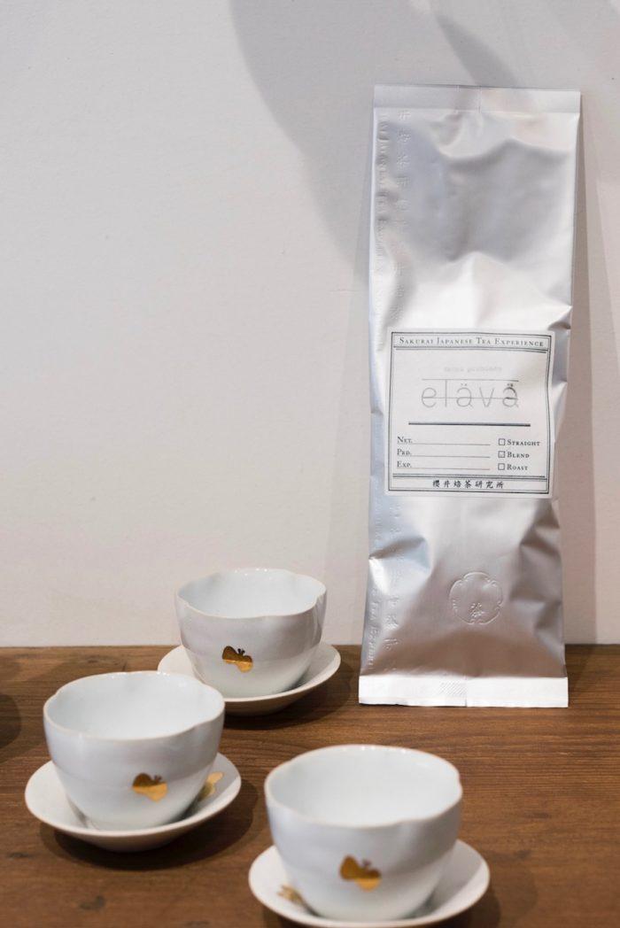 櫻井焙茶研究所によるエラヴァ オリジナルブレンドの茶葉と、陶作家 安藤雅信がミナ ペルホネンのために手掛けた花茶杯。