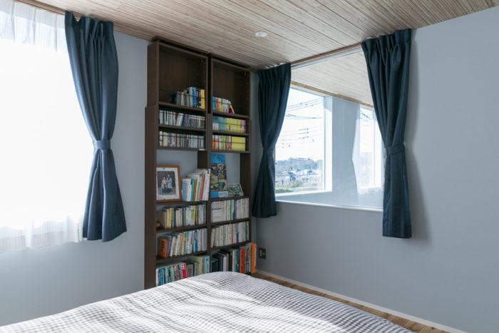 主寝室。吹き抜けに向いた窓があることで、開放的でユニークな空間に。