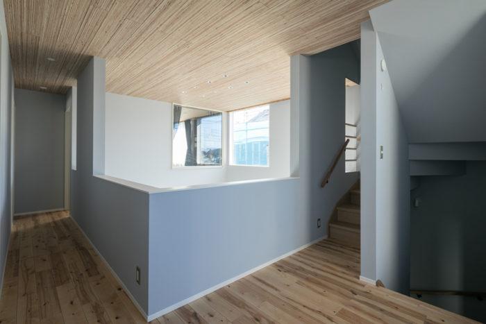 2階の廊下。LVL材の天井とグレーの壁紙がよくマッチしている。2階の床はバーチ材にして、1階とは少し表情を変えた。