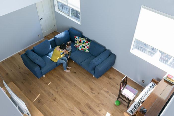 吹き抜けからリビングを見下ろす。1階の床は幅19cmの無垢のオーク材で、足に心地よい。