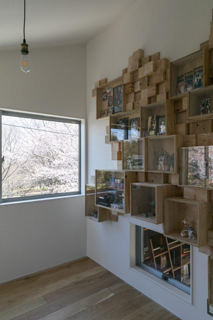将平さんの趣味屋。麻世佳さんがデザインした美術品のような壁面飾り棚に、プラモデルが並ぶ。この部屋からも桜が見える。