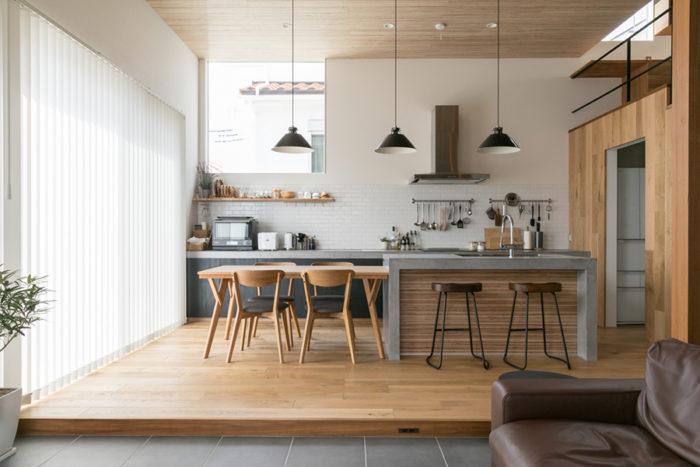 オリジナルの造作キッチン。「カウンター下の扉や照明を濃い色にして、空間をほどよく引き締めました」と麻世佳さん。「苦労しただけあって、見事な仕上がりなんですよ」と自画自賛の将平さん。