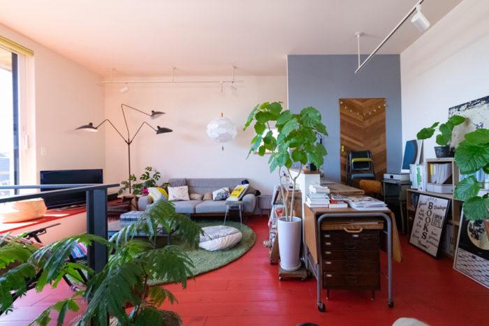パリの部屋を思わせる真っ赤な床は、パイン材にDIYでペイント。15年ほど愛用しているというセルジュ・ムイユの照明スタンドと、イケアのペンダントライトの組み合わせが素敵。窓際の段差はベンチとしても使える。室内にはたっぷりのグリーンを。