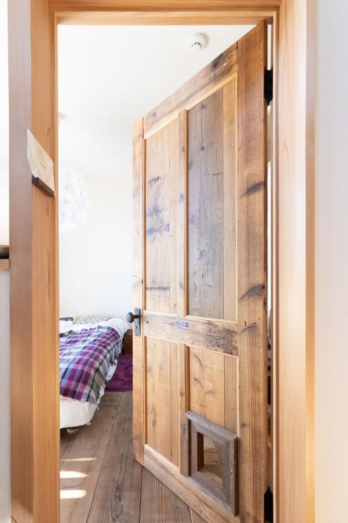 このドアがすべて手作りというから驚く。足場板を使い、ドアの下に額縁を使った愛猫のタンゴちゃんのための出入口もある。