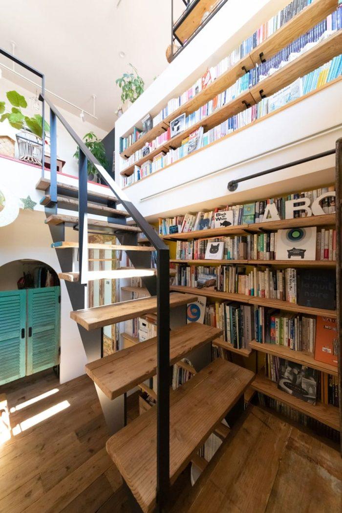 1階から2階への吹き抜けの壁はすべて本棚に。アイアンの手すりの階段。踏み板は古い足場板。