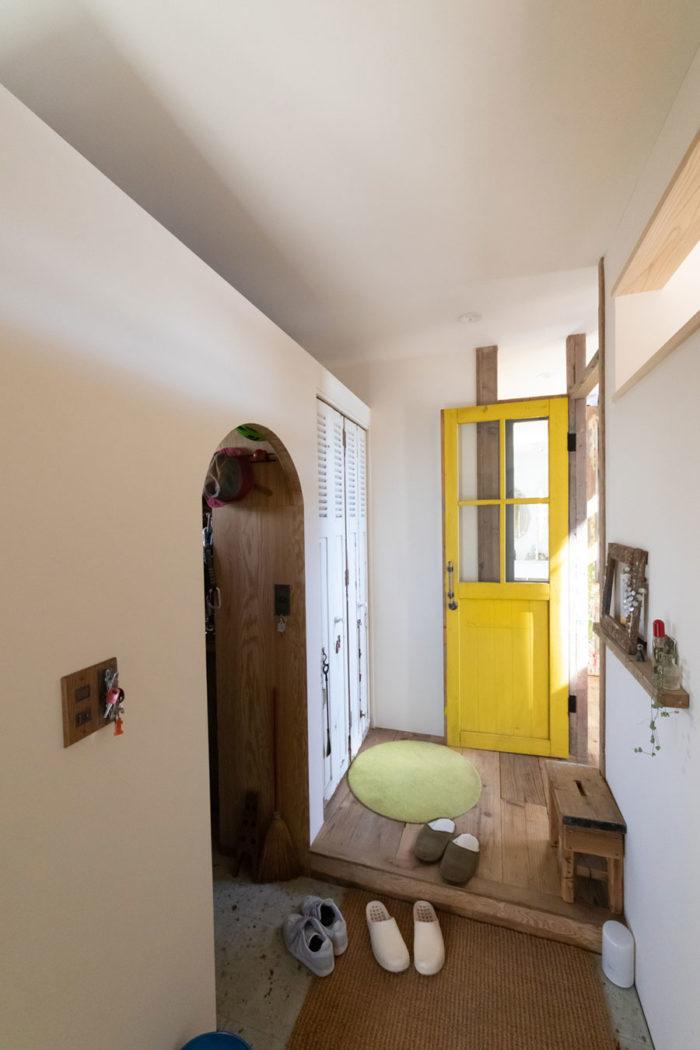 ネットオークションで手に入れたという黄色の扉が目を引くエントランス。左のアーチ型の奥のスペースは物入れになっている。