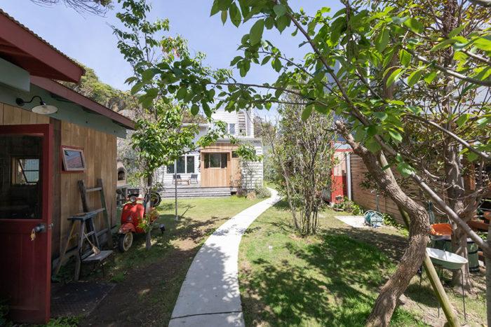 庭にはサボテンやオージープランツが。小径の奥にサーフハウスをイメージした白い家が建つ。