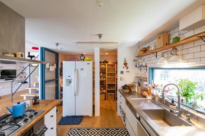 陽光あふれるキッチン。パントリーは冷蔵庫を挟んで両側から入れるように。キッチン台はシンクの横の台に段差があるのがポイント。このスタイルのステンレスの天板を見つけ、それに合わせて造作した。魚をさばいた後の掃除などがしやすい。