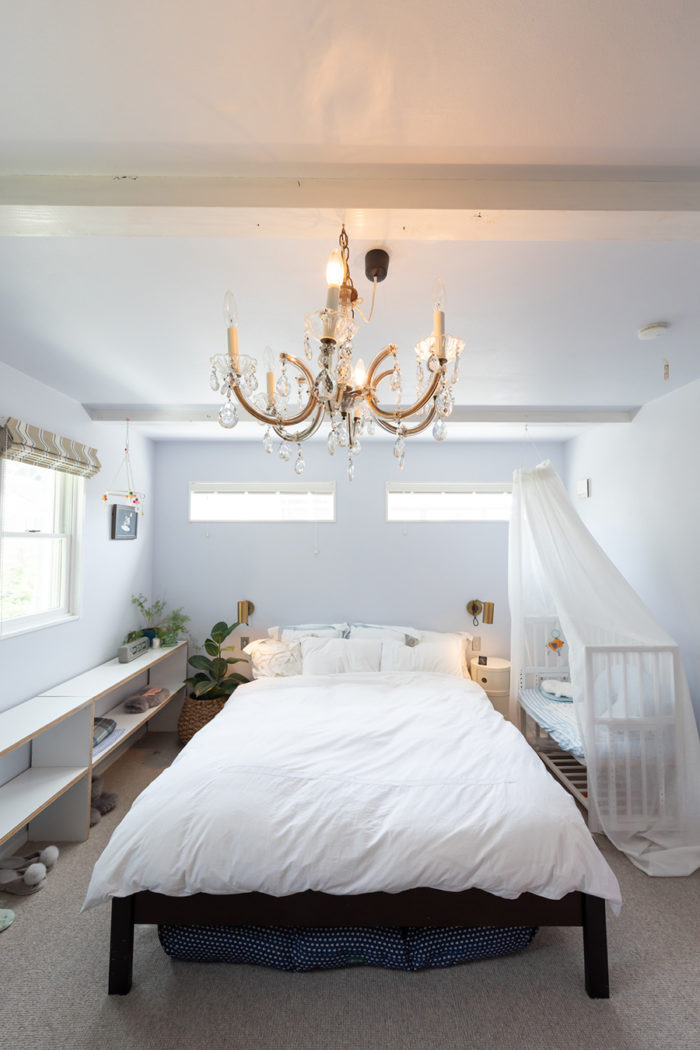 ベッドルームは落ち着けるようヨーロッパ風に。開口も控えめにした。ベッドサイドの照明など、海外のサイトで見つけて購入。壁は淡い水色にDIYで塗装した。