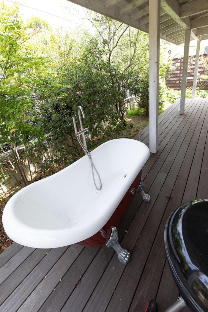 江ノ電がすぐそばを走るウッドデッキには屋外バスタブも。緑に包まれて入浴を楽しめる。