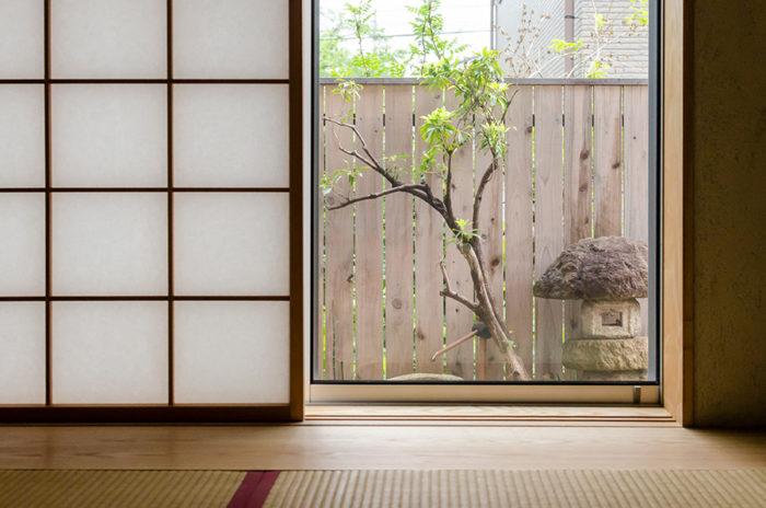 和室から灯籠の置かれた庭を見る。