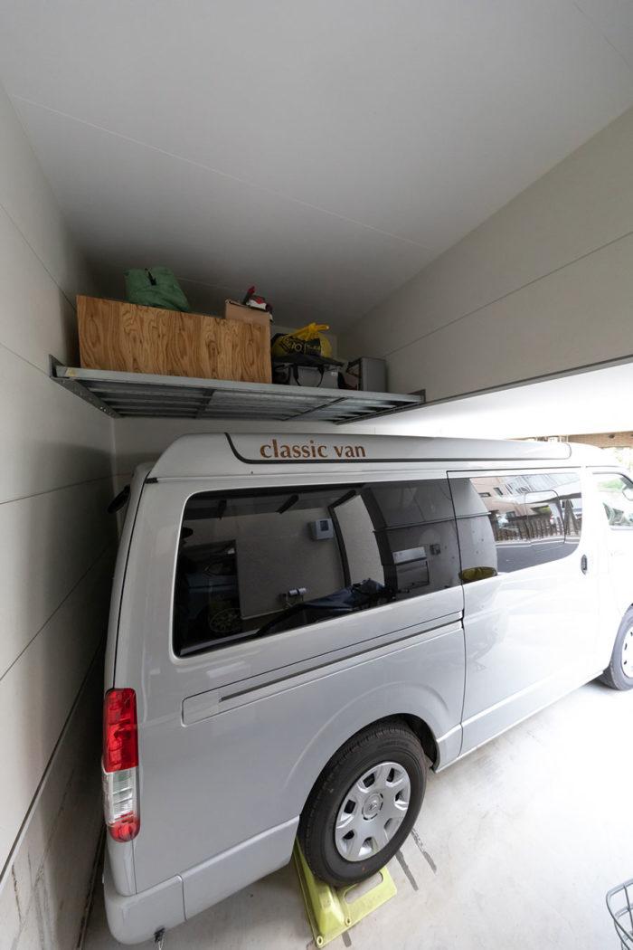 キャンピングカーの上部の棚は既製品の鋼製足場板を利用。アウトドアグッズが置かれている。