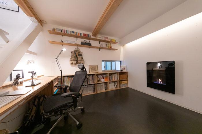 玄関奥にある書斎は80cm高くなっている。PCデスクや棚などすべてご主人が製作したもの。壁に取り付けたガス暖炉がオシャレ。
