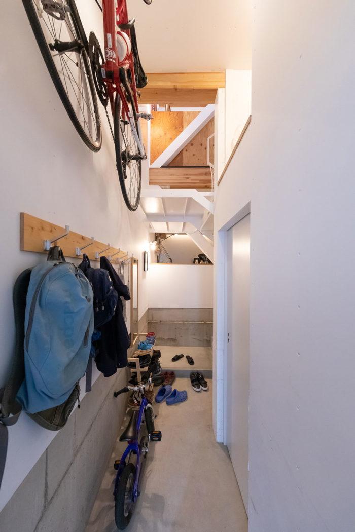 玄関を入って階段へ向かう通路。洋服掛けや自転車のフックはご主人がDIY。