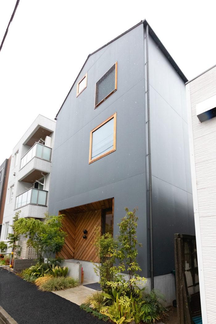 切妻屋根と四角い木製窓がかわいらしい外観。入口の左側に丸太の椅子があり、ウェイティングスペースになっている。