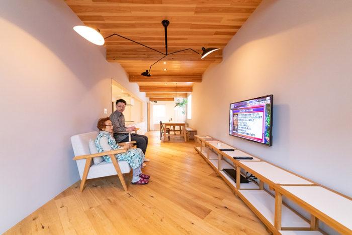 約30畳の広々とした空間。惠子さんが座っている椅子が「グリニッチ」のオリジナルソファ。テレビの下の棚は、この家の設計を手掛けた「TENHACHI」の製作。