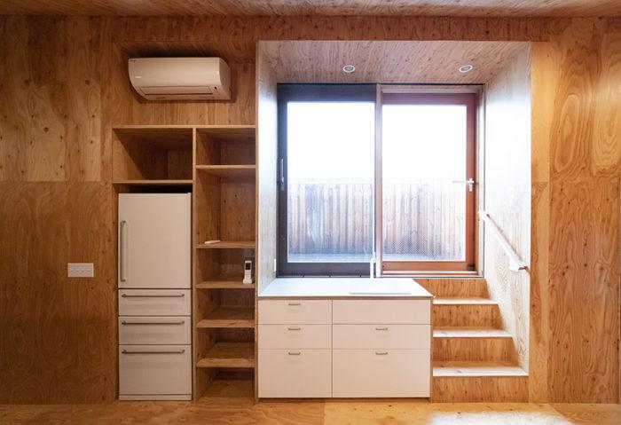 ミニキッチンや冷蔵庫も用意。木製サッシを開けると、日当たりのよいベランダへ。