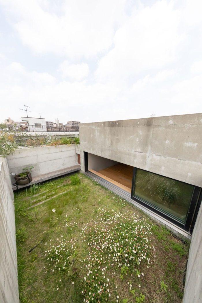 最上階の屋上の緑。ベンチの後ろのコンクリートのスラブの中にも深型のプランターがセットされている。