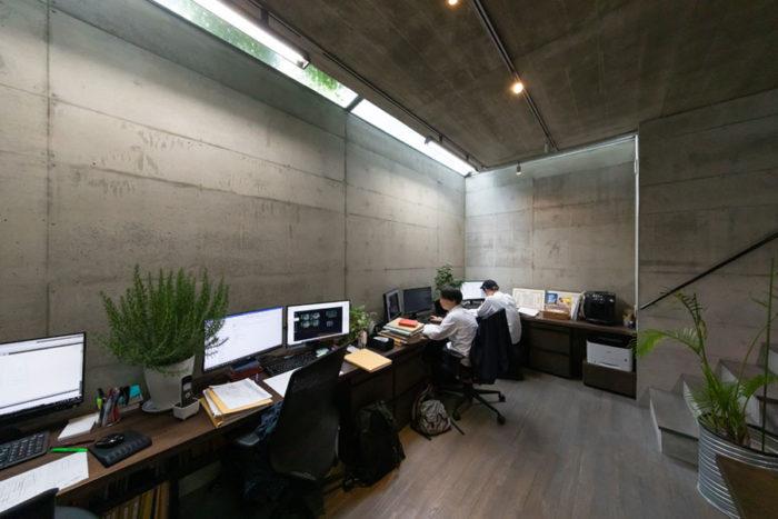 脩二さんの事務所。天井高3mのたっぷりとした空間。天窓からコンクリートの壁に落ちる光が美しい。