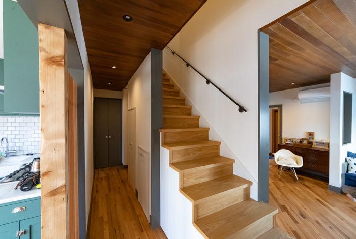 階段の上は吹き抜けになり、ここから家全体の気配がわかる。あえて設けた垂れ壁は、床の変化とともに空間を緩やかに分けるためのもの。アイアンの手すりは、グリップ感にこだわって加工した。