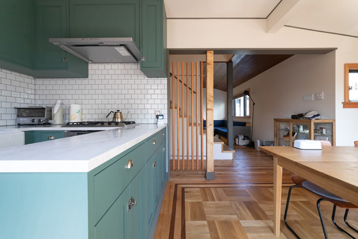 モスグリーンのキッチンが、シンプルな内装のアクセントに。ダイニングの床は市松模様の寄せ木張りで変化をつけた。