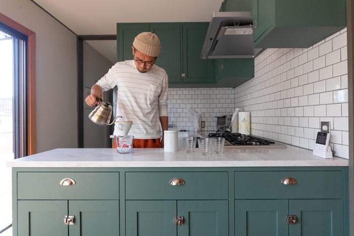 人造大理石の天板のキッチンには、収納もたっぷり設けた。白いサブウェイタイルに、目地はグレー系を選択。