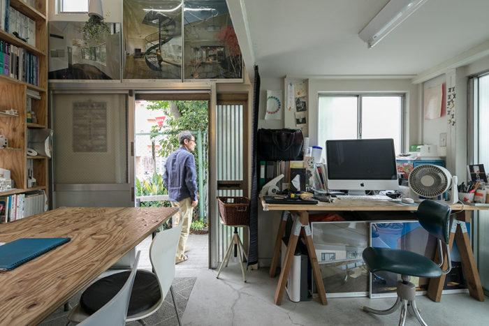 1階の入り口と、七島さんの仕事場。右側の天井高は2mほどと低い。左側は吹き抜け。