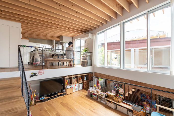 リビングから見る。奥さんの希望で大きな開口がつくられた。天井には奥さんが好きという木製の梁がリビングからキッチンまで整然と並ぶ。