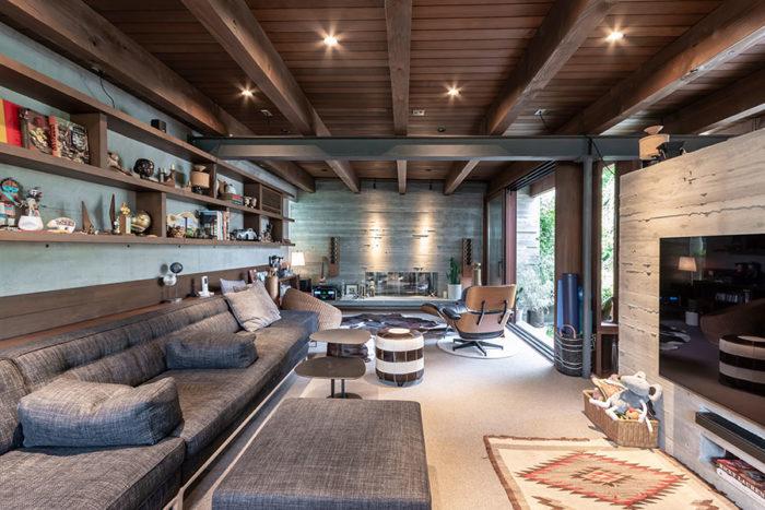奥にこの部屋のために製作されたオリジナルスピーカーの置かれたリビング。天井をやや低めに抑え落ち着いた色合いのこのスペースはしっとりとした大人の空間。