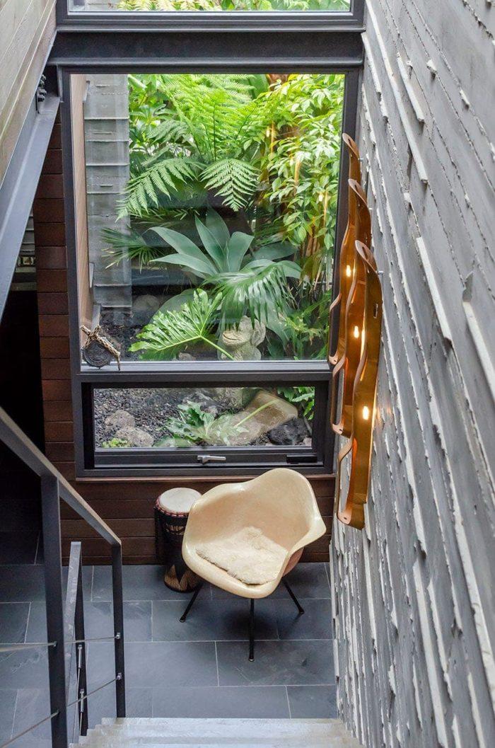 階段途中からイームズのアームシェルチェアを見下ろす。開口を通して見える緑もSOLSOのプラニングによるもの。