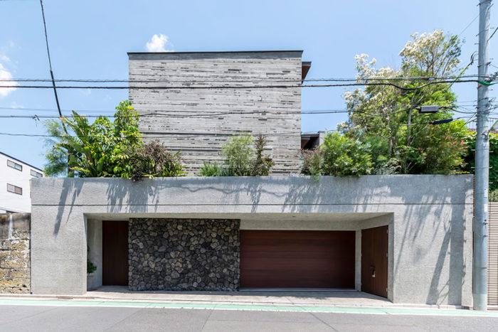 道路から見た外観。コンクリート、石、木の素材感の対比が生きている。右に白い花が咲いているのが見えるのがスノーインサマーの木。右の木の部分が地下1階のガレージ。