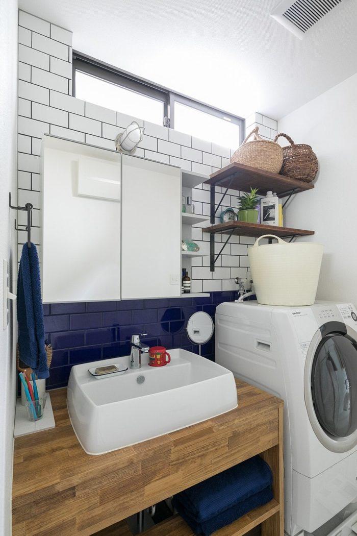 高窓から洗面所に明るい光が射し込む。ブルーのタイルをアクセントに。タオルもブルーでコーディネイト。