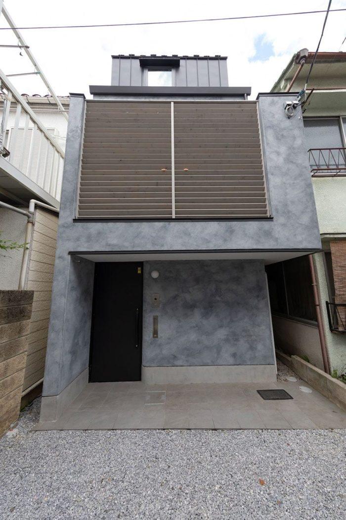 住宅密集地に建つ。マーブル模様の外壁は左官コテ塗仕上げで落ち着いた雰囲気。2階のバルコニーに設置した木製ルーバーの羽根の角度にこだわり、道路からの視線をカット。