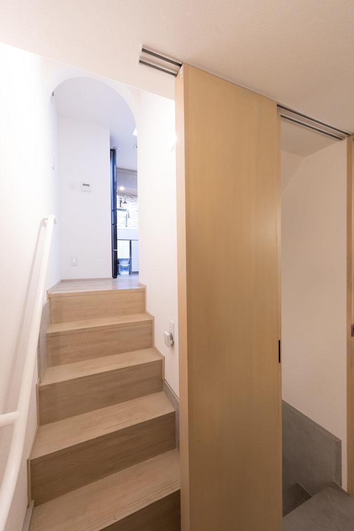 扉の奥には地下の寝室へと続く階段があり、まるで隠し部屋のよう。扉は階段のほうまで開くため、大きな荷物も搬入可能に。左の階段を昇るとダイニングキッチンへ。