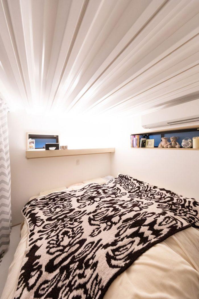 半地下にある寝室は、1年中安定した気温で快適。造作棚には間接照明を組み込み、演出効果を。