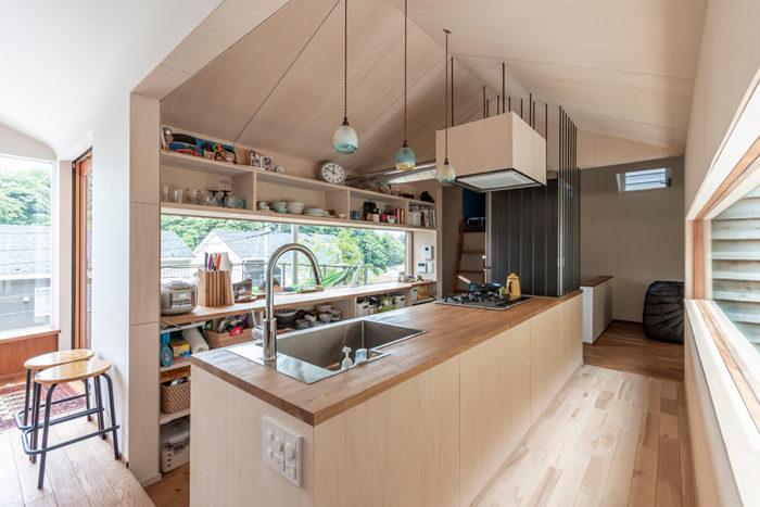 家の中心に位置するキッチン。食事をつくる際にも裏山の緑が眼に入る。左右の空間とは天井の仕上げを変えている。このキッチンで家族間のコミュニケ―ションが以前よりも活発になったという。キッチンの奥にロフトが設けられている。