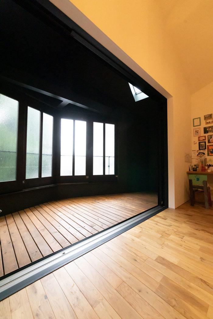 窓を閉めれば、バルコニーがリビングの一部に。アンティークな型板ガラスが、レトロな雰囲気も添える。