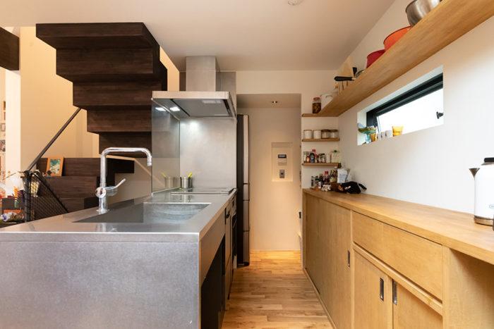 キッチンは掃除のしやすいステンレスで造作。高さを揃えて収納棚も造り付けに。奥にはパントリーを設けた。