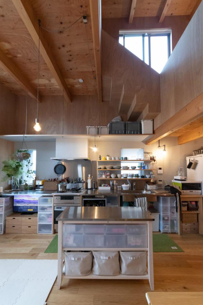厨房のようなキッチンがリビングと一体に。正面上はワークスペースから子ども部屋に上がる階段。