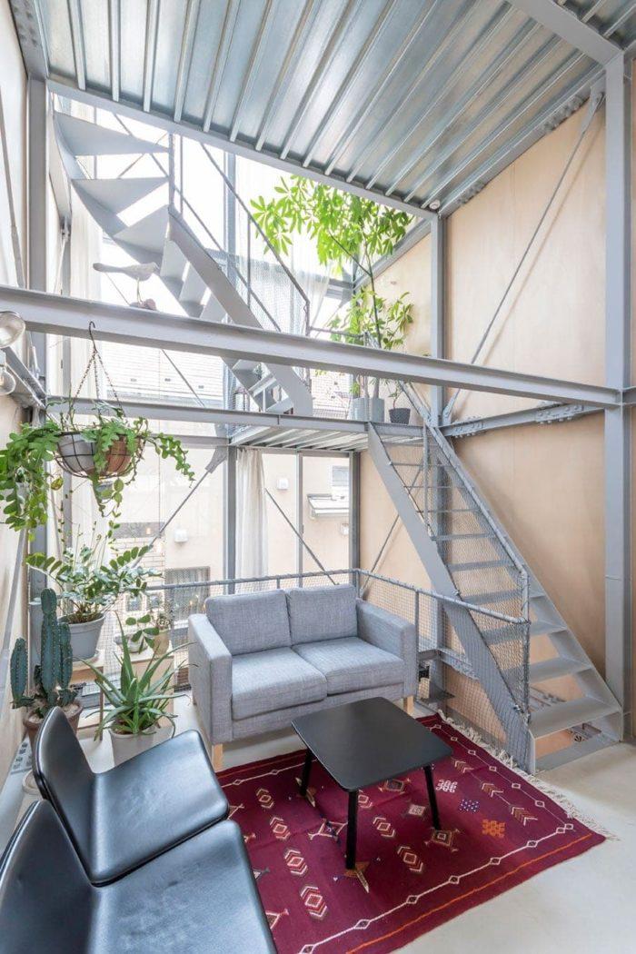 玄関入ってすぐのソファの置かれたスペース。階高は2.2mで鉄骨造の部分はペントハウスを含めて4層ある。