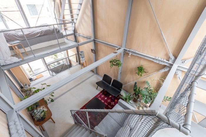 踊り場から1階を見下ろす。寝室に行くには1階上がってから階段を下る。トイレ以外は閉じた空間がなく1階のスペースを中心に広がりの感じられるつくりになっている。