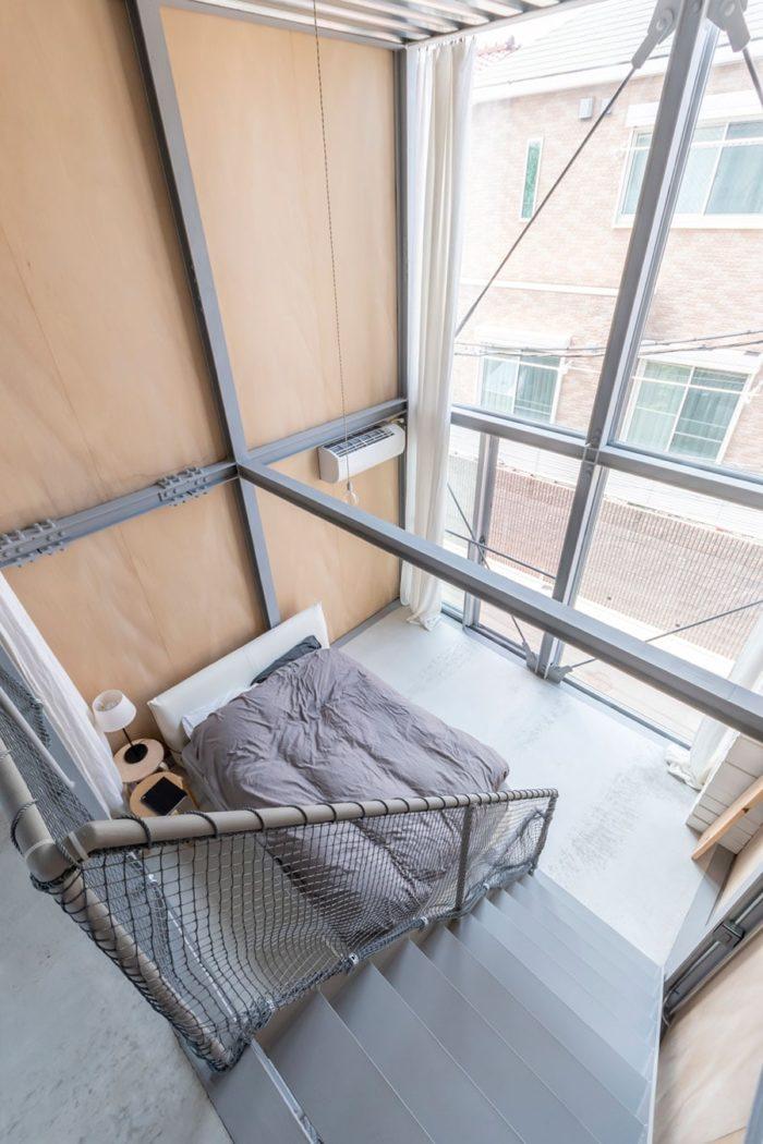 寝室を見下ろす。壁の明るいシナ合板は、鉄骨部分のグレーを考慮し、かつ空間に温もり感を与えるための選択。