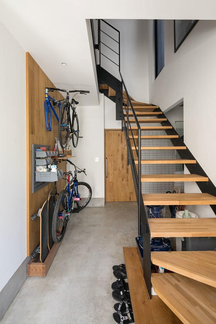 1階はもともと倉庫として使われていたのだそう。玄関のモルタルを奥まで伸ばし、土間のように使えるスペースに。オーク材を貼った壁面に自転車ラックを設置。階段は新設した。